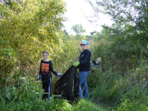 Adult and children cutting down teasel an invasive plant