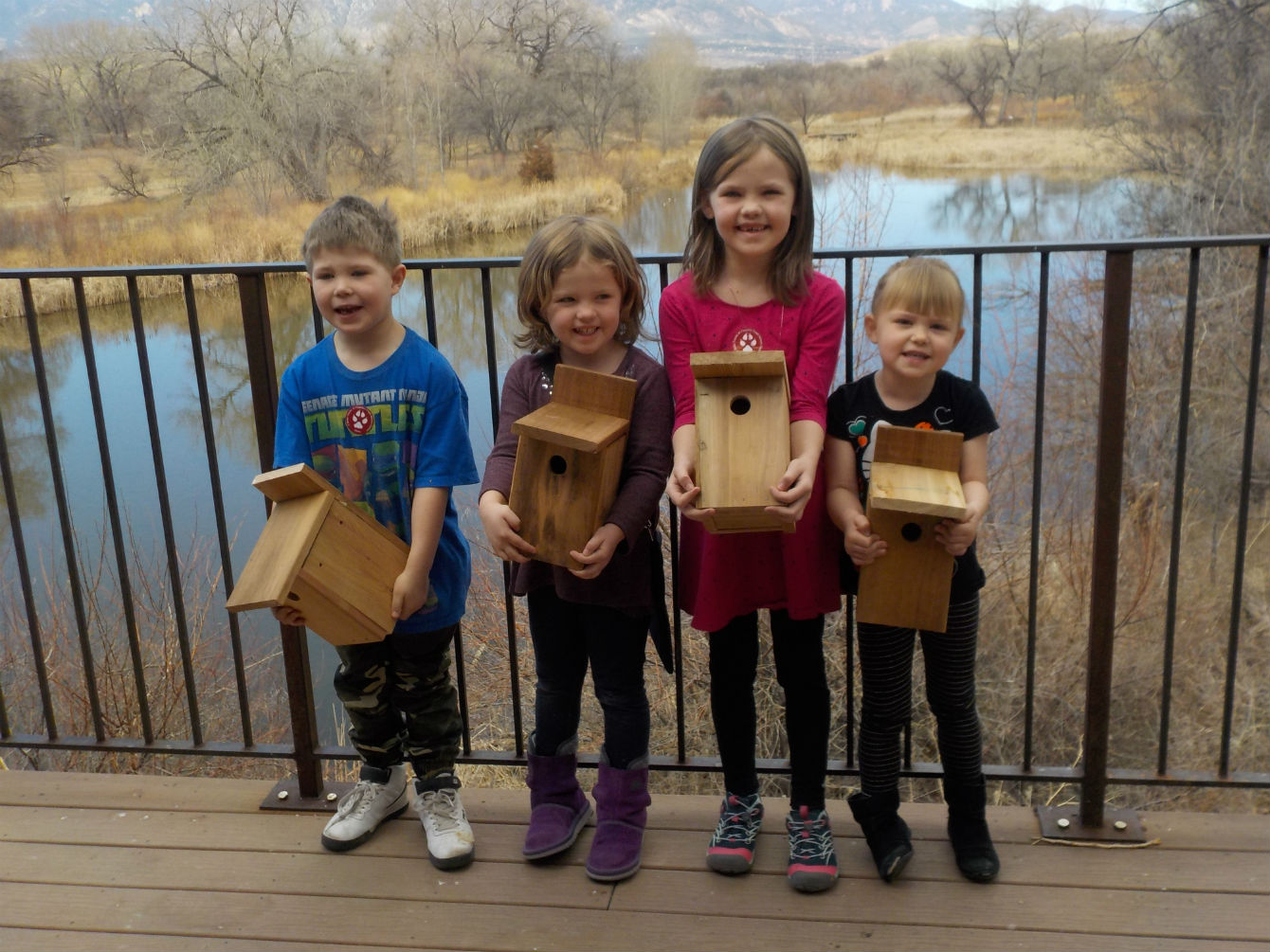 Children holding birdhouses they made on the deck of the nature center
