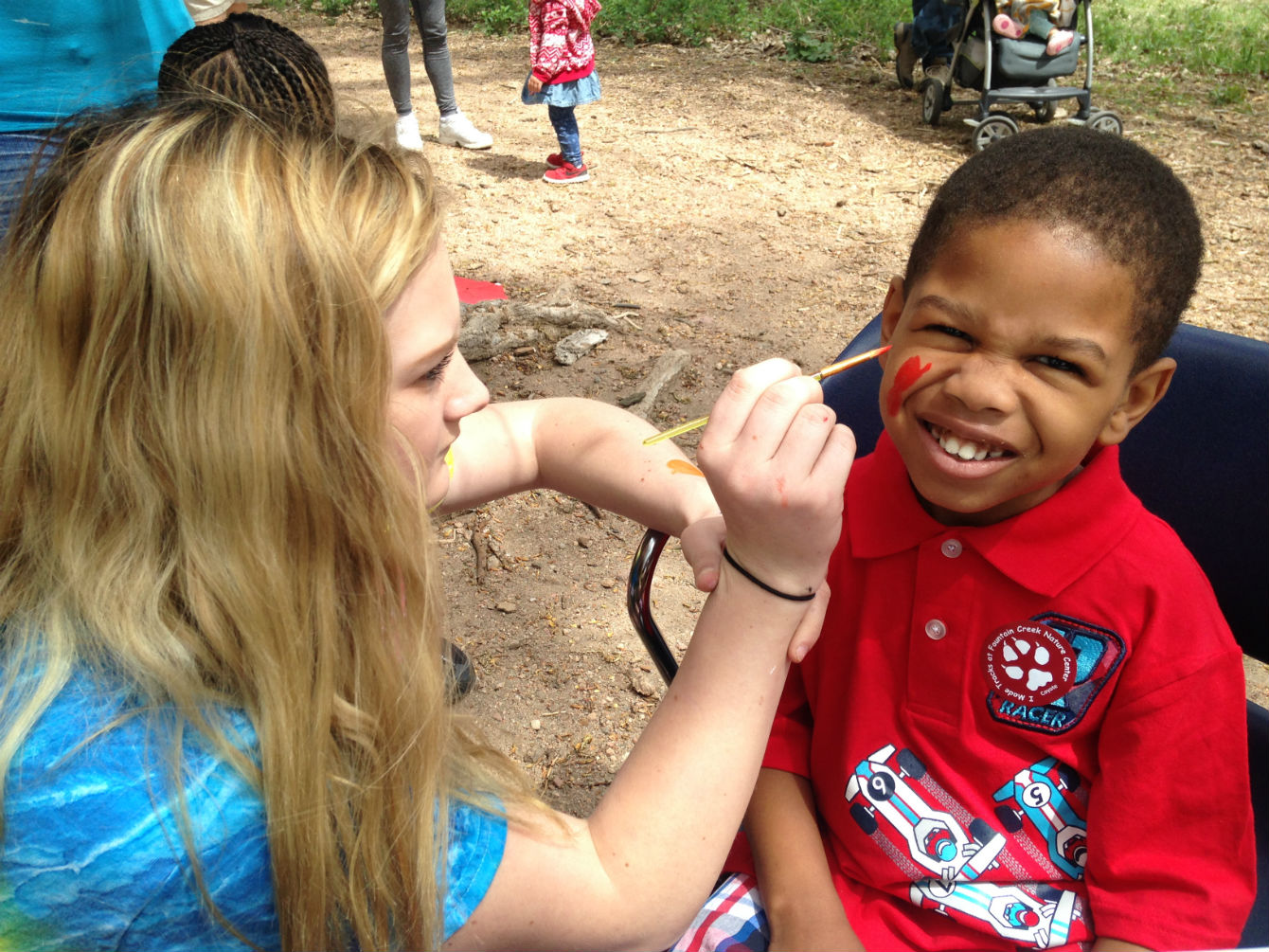 Volunteer painting a childs face