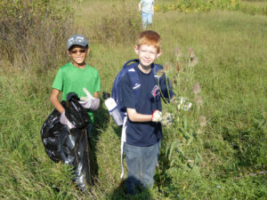 children cutting down the invasive plant teasel